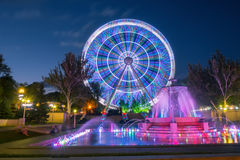 City Ferris wheel with a fountain in the evening in the Park Royalty Free Stock Images