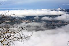 The city in a foggy haze. Panoramic view of the city from huge height, through clouds and trees royalty free stock images