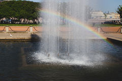 City fountain in a bright sunny day with a rainbow through it Royalty Free Stock Image