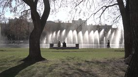 City fountain. Footage. People walking in the park. Fountain in city park on hot summer day. Stream of water, drops and. Bright splashes of water in beautiful stock footage