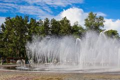 City fountain in the park. Bright sunny day, heat. Large city fountain, high streams of water, white splashes. In the distance are tall green trees, benches stock photos