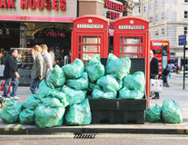 City Garbage. Green garbage bags piling up next to telephone boots in London Stock Images