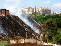 City Garbage. A garbage depot in a city set on fire adding to the pollution Stock Images