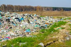 City garbage dump with domestic. And garbage waste outside the city next to the agricultural economic field royalty free stock photography