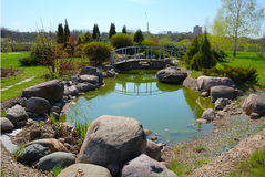 City garden. Small pond with rocks and arched bridge in city garden royalty free stock image