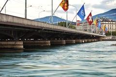 City of Geneva in Switzerland. Mont Blanc bridge with waving flags in Geneva Switzerland Stock Photos
