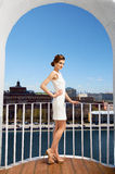 City girl on the balkony. Young lady fashionably dressed standing on the balcony in a sunny spring day enjoying beautiful city panorama stock photo