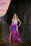 City girl. Beautiful young girl in a purple dress in the city Royalty Free Stock Photo