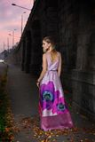 City girl. Beautiful young girl in a purple dress in the city Stock Image