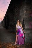 City girl. Beautiful young girl in a purple dress in the city Stock Photography