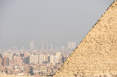 City of Giza. View at the city of Giza in Egypt, emerging from polluted air, seen from the Giza Necropolis with part of the pyramid visible Stock Image
