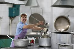 Cook with a ladle. City of Gomel Belarus 01 June 2017. Industrial kitchen in a medical hospital. Woman cook in an industrial kitchen pours a drink into the royalty free stock photos