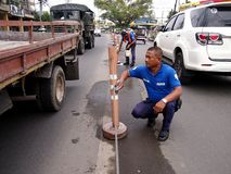 City government workers clean road safety poles. ANTIPOLO CITY, PHILIPPINES - AUGUST 16, 2016: Workers from the Office of Public Safety and Security (OPSS) under Royalty Free Stock Photos