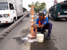 City government workers clean road safety poles. ANTIPOLO CITY, PHILIPPINES - AUGUST 16, 2016: Workers from the Office of Public Safety and Security (OPSS) under Stock Photography