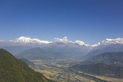 City in a green mountain valley on the background of the Annapurna snow ridge under a clear blue sky. A city in a green mountain valley on the background of the stock image