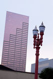 City grotesque old and new style modern and Baroque Portland. Lamppost with two glass lanterns patterned shapes against high contemporary skyscraper with pink Stock Images