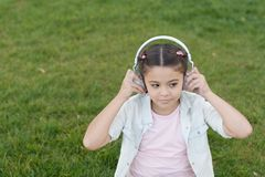 City guide and audio tour. Girl little tourist kid using audio guide mobile application. Audio tour headphones gadget. Free style of travelling. Exciting stock photo