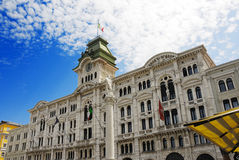 City Hall. Perspective of the Palazzo Comunale (City Hall) in Trieste, with a beautiful clock tower and two bronze statues Stock Photos