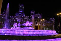 City Hall building and Cibeles fountain illuminated in purple for Women's Day stock images