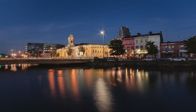 City Hall, Cork, Ireland at night. City Hall of Cork, Ireland illuminated at night reflecting in waterfront Stock Photography