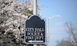 City Hall, Police and Fire Department. A sign points to the center of a city downtown where the police station, fire department and city hall all reside in a royalty free stock image
