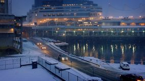 City Harborside Scene With Snow Falling In The Evening. Pretty harbor scene with person walking by road as cars pass in snowfall stock footage