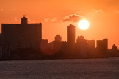 The city of Havana at sunset with the sun setting over seaside highrise buildings Stock Photography