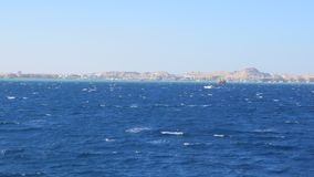 The City of Hurghada. Is Located Along the Red Sea. The Boat is Quite Far Away From the Shore. Two Boats are Sailing Against the Background of the City stock footage