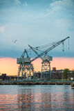 City industrial area with port cranes at sunset time. Royalty Free Stock Images