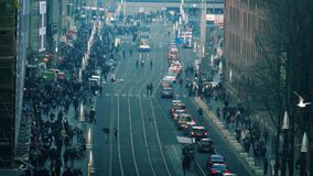 City Intersection With Huge Crowds Of People. Cars and trams on a major road through the city with crowds on the street stock footage