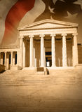 City Justice Law Courthouse with Flag. A city courthouse law building with pillar columns and stairs. An American flag is in the background. Can represent law Royalty Free Stock Images