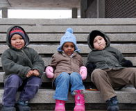 City Kids. Three children sitting on the city steps on a winter day Stock Images