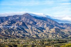 City of Lake Elsinore. A view of a small city in Lake Elsinore framed against a rugged mountainside stock image