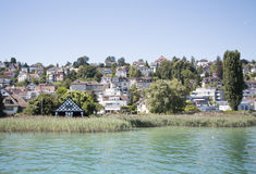 City by the lake. A city with houses right beside the lake with plush greenery all around blue sky green waters Royalty Free Stock Photos
