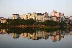 City lake and public park in Hanoi, Vietnam. Public city park near Tay lake in the downtown district of Hanoi, Vietnam. Residential houses reflected in water Royalty Free Stock Images