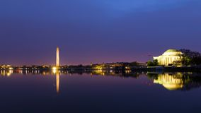 Washington DC panorama around Tidal Basin at sunrise during cherry blossom. City landmarks with reflection in dark waters at dawn Royalty Free Stock Photos