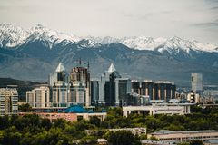 City landscape on a background of snow-capped Tian Shan mountains in Almaty Kazakhstan. City landscape on a background of snow-capped Tian Shan mountains. The stock photography