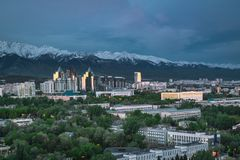City landscape on a background of snow-capped Tian Shan mountains in Almaty Kazakhstan. City landscape on a background of snow-capped Tian Shan mountains. The royalty free stock photo