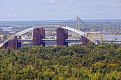 City landscape with bridges and trees against the sky. Bridges across the river and green trees against the sky Royalty Free Stock Images
