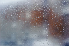 City landscape is hardly distinguishable through a muddy window with rain drops Stock Image