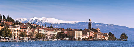City landscape on lake. An Italian city landscape (Salò) on the lake of Garda with the whiten mountains behind Royalty Free Stock Photography