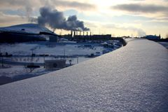 Winter landscape in a megacity. City landscape with a lot of pipes and steam coming from them Royalty Free Stock Photos