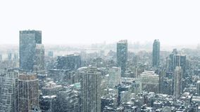 City Landscape In Snowstorm. Wide view over city with snow on rooftops in heavy snowfall stock video
