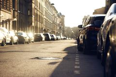 The city landscape of the street on which there are parked cars stock images
