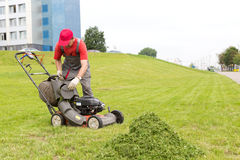 City landscaper unloading grass from lawn cutter bag. City landscaper worker man stop mower machine and unloading grass from lawn cutter bag Royalty Free Stock Photography