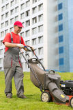 City landscaper worker cutting grass. Senior city landscaper worker cutting grass with self-propelled push lawn mower machine Stock Images
