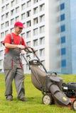 City landscaper worker cutting grass. Senior city landscaper worker cutting grass with self-propelled push lawn mower machine stock images