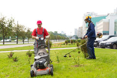 City landscapers gardeners mowing lawn. With gas trimmer and lawnmower machine Royalty Free Stock Photography