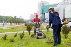 City landscapers gardeners mowing lawn. With gas trimmer and lawnmower machine stock photography