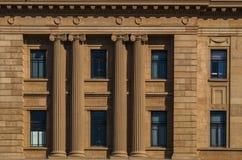 City 1. Large columns framing windows in light tan masonary Stock Photos